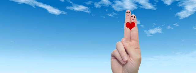 Conceptual fingers in love over blue sky banner