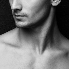 Male beauty concept. Half-face portrait of muscle young man posi