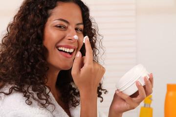Frau cremt sich ihr Gesicht ein