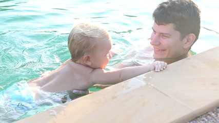 father and small girl child is play by the edge of the pool