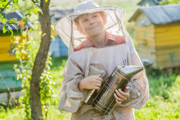 Young beekeeper using a smoker on bee yard