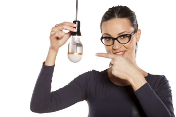 young woman pointing on LED bulb and showing thumbs up