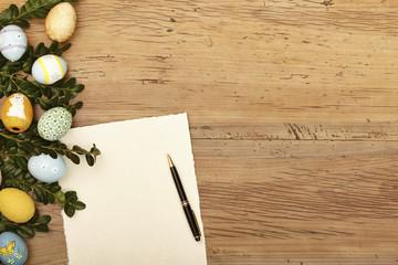 Ostereier und Zweige, leere Karte und Kugelschreiber auf Holz