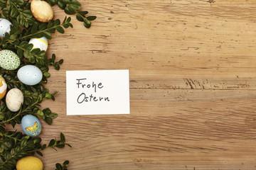 Karte, Frohe Ostern, Ostereier und Zweige auf Holz