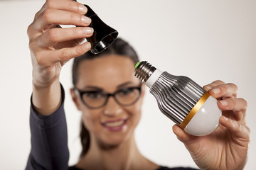 young woman mount LED light bulb in the socket