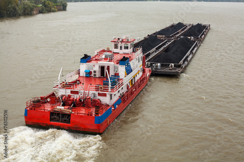Tugboat Pushing a Heavy Barge - 76302516