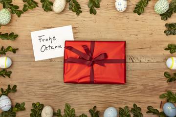 Osterdekoration, Karte, Frohe Ostern und rotes Geschenk