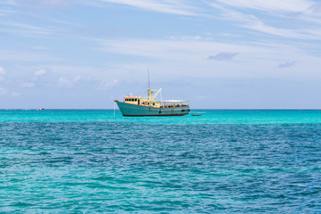 Yellow and White Fishing Boat in Aqua Water