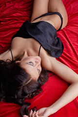 Tempting brunette lying on silk sheets