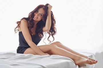 Studio shot of happy brunette posing in negligee