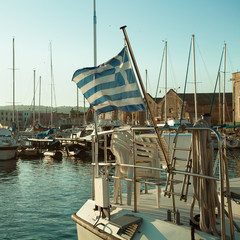 Port, the Greek flag and boats. Impressions of Greece