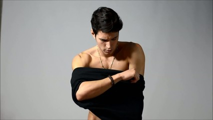 Handsome young man dressing, putting on t-shirt
