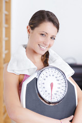 young brunette fitness woman with scale