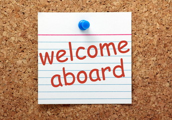 Welcome Aboard printed index card on a notice board