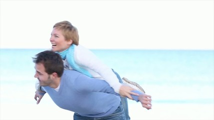 happy young couple piggibacking on the beach