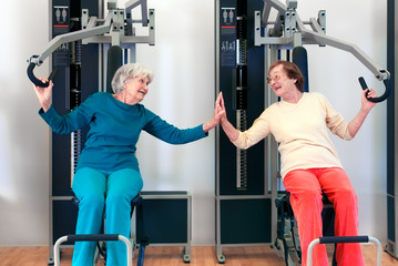 Happy Grannies Enjoying Chest Press Exercise.