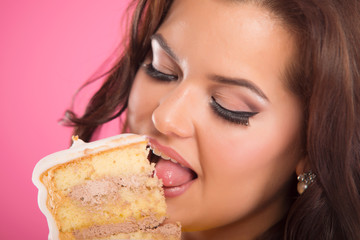 Pretty young woman eating cake.