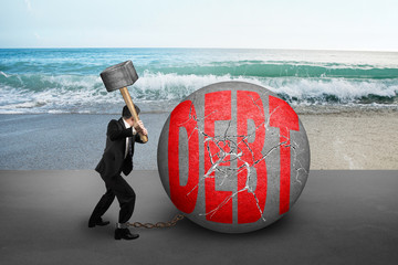 businessman holding hammer hitting cracked DEBT ball with sea be