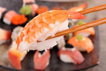 Prawn sushi held by chopsticks