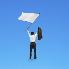 A businessman waving blank white flag isolated on blue