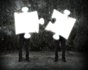 Glowing puzzles businessmen hold to connect illuminating dark co