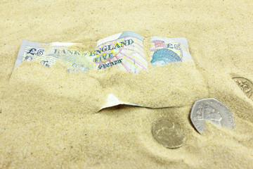 British Currency buried by sand.