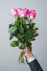 Bouquet of pink roses in a male hand