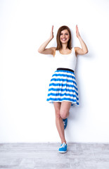 Full length portrait of a cheerful woman posing at studio