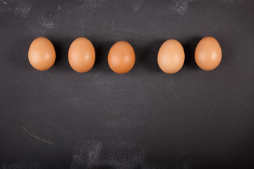 Eggs on dark chalkboard with copy-space
