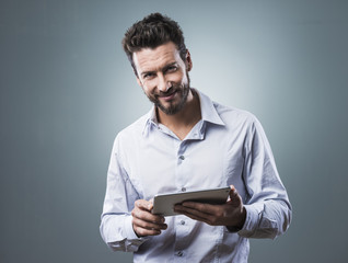 Smiling confident man with tablet