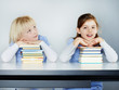 Two cute girlfriends learning with books