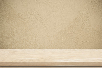 Empty wooden table over grunge cement wall.