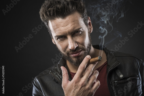 Leinwandbild Motiv Confident fashionable man with cigar