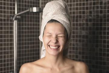 Grinsende spitzbübische Frau steht in der Dusche