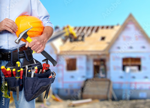 Construction worker with hammer and tools. - 76315545
