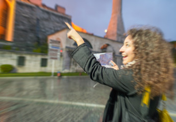 Blurred zoomed view of a happy girl pointing to a Istanbul landm