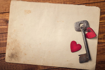 Old key with a heart of wood on paper background