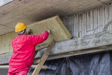 Man installing external wall insulation
