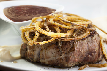Grilled steak with caramelized onion rings