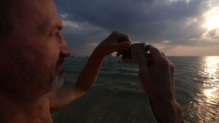 elderly man photographs the sunset on the camera at sea