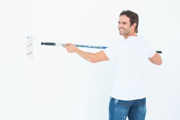 Happy man using paint roller