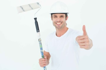 Man holding paint roller while gesturing thumbs up