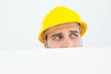 Repairman looking away while in front of billboard