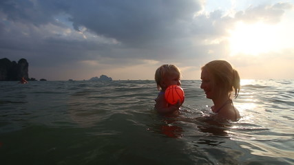 little girl with her mother bathed in the sea at sunset