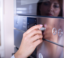 Female hand on oven knobs
