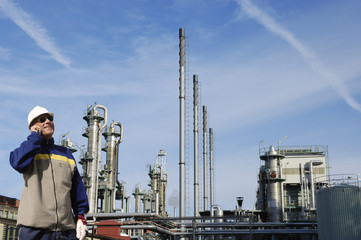 oil worker in front of large refinery industry