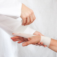 Nurse cover the hand of patient by bandage