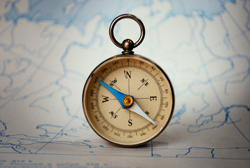 Magnetic compass standing upright on a map