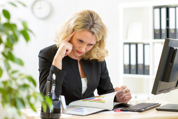 middle-aged business woman working in office and examining