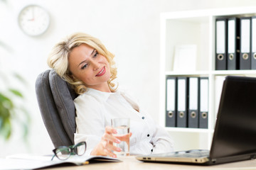 senior business woman relaxing at work in office